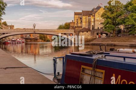 A view down the River Ouse towards Lendal Bridge and the City skyline.  A barge is in the foreground. - Stock Photo