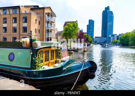 A homely houseboat mooring on the Regents Canal with luxury residential skyscrapers in the background, London, UK - Stock Photo