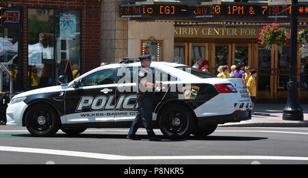 Policeman assisting in traffic and crowd control, Activities and people during Wilkes Barre PA's.Thursday farmers market on the public square 7-12-18 - Stock Photo