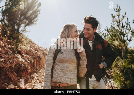 Couple in love on a mountain hike. Man and woman with backpack walking on mountain trail and looking at each other smiling. - Stock Photo