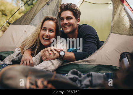 Attractive couple lying in their tent looking away and smiling. Loving young couple relaxing in tent. - Stock Photo