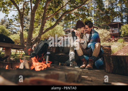 Couple in love sitting near a bonfire at campsite. Man and woman caught in a romantic moment at campsite. - Stock Photo