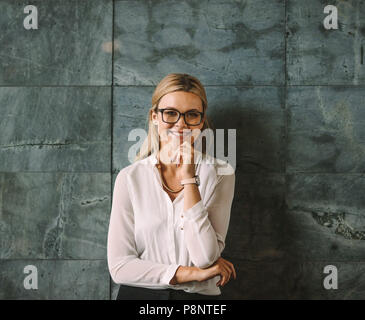 Portrait of beautiful young woman in formal wear standing against grey wall and smiling. Businesswoman with glasses looking at camera with hand on chi - Stock Photo