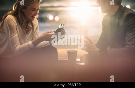 Smiling business colleagues using their smart phones during coffee break in office. Business man and woman sitting in office lounge with their mobile  - Stock Photo