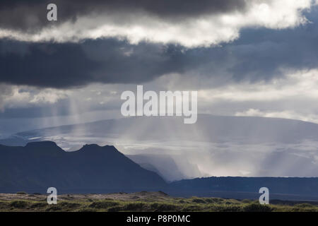 Rain falling from dark clouds under a different angle than the suns rays shining through these clouds - Stock Photo