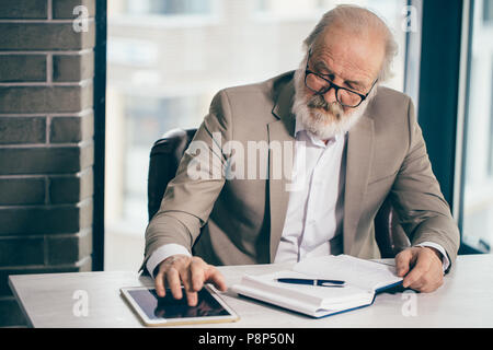 close up photo of handsome grey-haired senior businessman working with tablet in the loft office - Stock Photo