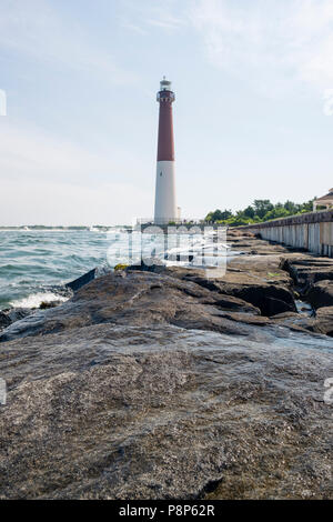 lighthouse in New Jersey provides warning light on island for ships navigating through ocean channels - Stock Photo