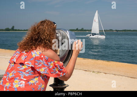 woman uses coin operated binocular to observe landscape, ocean, boats, beach scenes at the coast - Stock Photo
