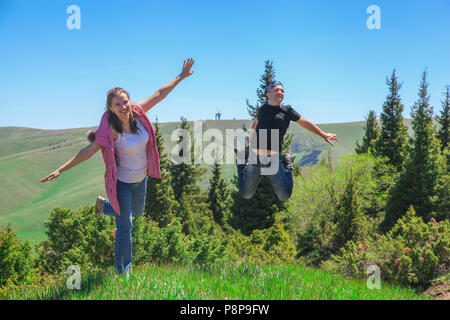 A happy couples. Woman in a pink waistcoat and blue jeans spread her arms and jumps on one foot. A man with a smiley face jumps on both feet - Stock Photo