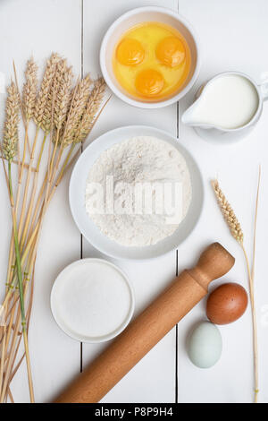 Wheat and baking ingredients on a white wooden background - Stock Photo