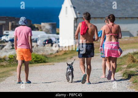 A group of holidaymakers walking on a footpath on The Headland in Newquay in Cornwall. - Stock Photo