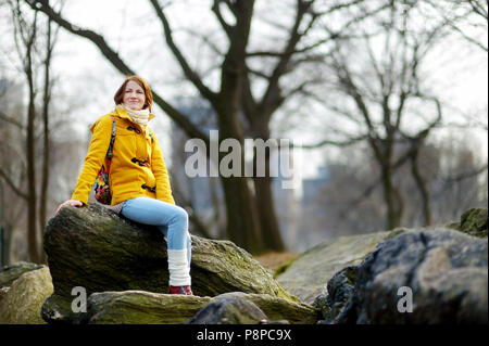 Beautiful young woman looking at skyscrapers while sitting on a rock in Central Park, New York - Stock Photo