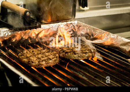 hamburger beef patty - grilled meat and cheese on a barbecue grill fire - Stock Photo