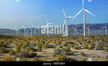Wind turbine farm in California desert with backdrop of mountains - Stock Photo