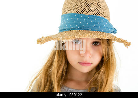 Adorable pretty little girl with big soulful eyes looking out from under the wide brim of a straw hat at the camera with a solemn expression, isolated - Stock Photo
