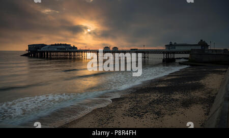 Cromer pier with clouds at sunrise, Norfolk, England - Stock Photo
