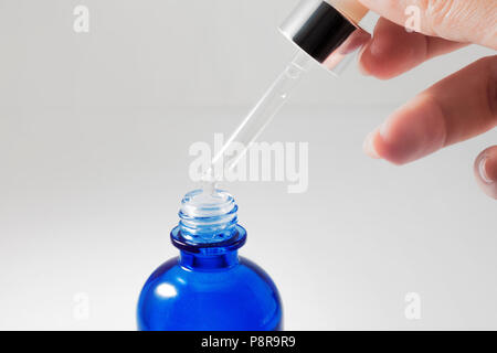 Use the serum, cosmetics. Female hand holds the pipette with cosmetic serum. Close up - Stock Photo