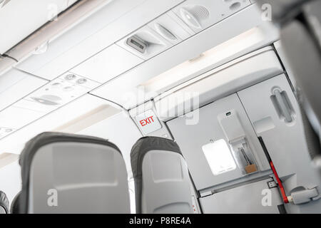Emergency exit on an aircraft, view from inside of the plane. Empty airplane seats in the cabin. Modern Transportation concept. Aircraft long-distance international flight - Stock Photo