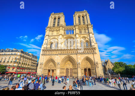 Paris, France - July 1, 2017: many tourists in square of Notre Dame de Paris, Ile de la Cite, while they wait to visit the famous gothic church. Sunny day, blue sky. Main facade of Cathedral of Paris. - Stock Photo