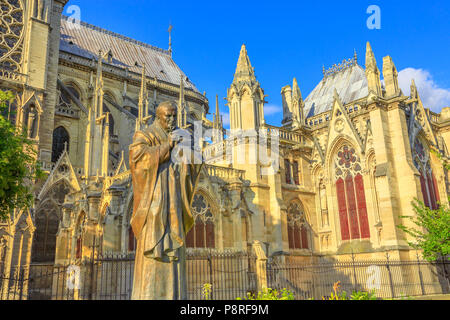 Details of Pope John Paul II statue on side of church Notre Dame of Paris, France. Gothic architecture of Cathedral of Paris, Ile de la cite. Beautiful sunny day in the blue sky. - Stock Photo