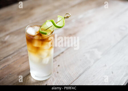 Dark and Stormy Rum Cocktail with Ginger Beer and Lime garnish. Glass of Dark and Stormy Cocktail drink on wooden table, copy space.