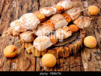 Turkey meat on barbecue grill,cooked on skewers with apricot .BBQ - Stock Photo