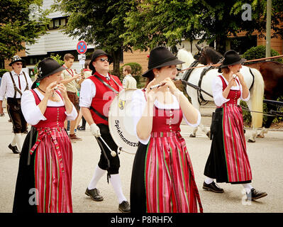 GARCHING, GERMANY-JULY 8, 2018. Young women in Bavarian costume perform playing flutes at the traditional parade in Garching university town near Muni - Stock Photo