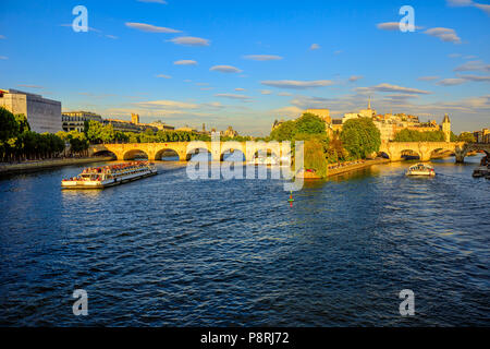 Tourist cruise on Seine river. Bateau mouche from Pont Neuf bridge and Notre Dame church on background. Tourist travelers in popular landmarks of Paris in France at sunset from Pont des Arts bridge. - Stock Photo