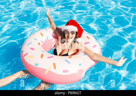 bikini girl in christmas hat with sunglasses relaxed on pink inflatable pool ring. - Stock Photo