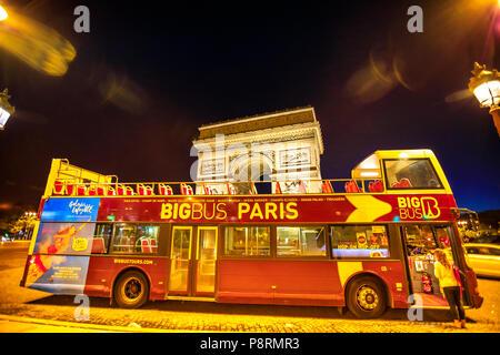 Paris, France - July 2, 2017: touristic bus at Champs Elysees with Arc de Triomphe at night in Paris on background. Hop-On Hop-Off Tour, Paris. Explore top Paris attractions. Night urban scene. - Stock Photo