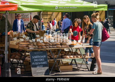 A small food market outside Kings Cross with baked breads and other produce for sale with customers browsing goods, London, UK - Stock Photo
