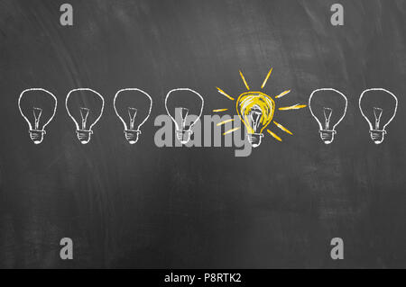 Smart creative idea concept drawing on blackboard or chalkboard with bright yellow light bulb sketch - Stock Photo