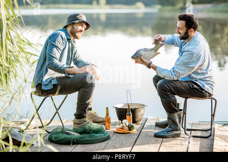 Two friends sitting together with beer and fish on the picnic while fishing near the lake - Stock Photo
