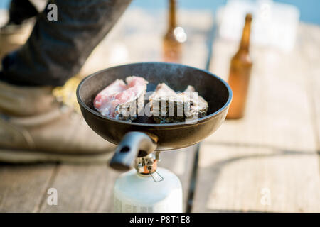 Frying two fish steakes on the burner during the picnic with beer and fishing tackles outdoors - Stock Photo