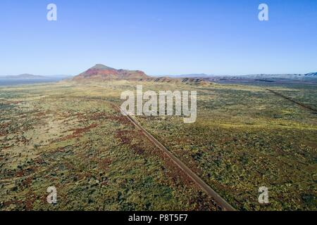 Aerial view of great northern highway and Mount Bruce in outback landscape, Karijini National Park, Pilbara, Northwest Australia | usage worldwide - Stock Photo