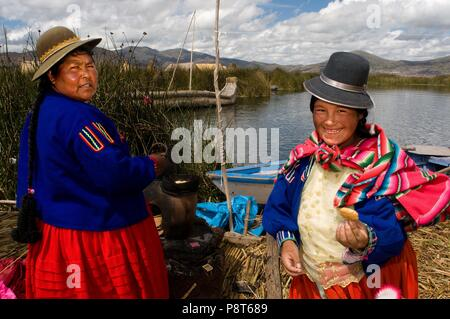 Uros Island, Lake Titicaca, peru, South America. Two women dressed in typical regional costumes on one of the Uros islands. January 2018   usage worldwide - Stock Photo