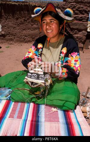 A woman from the village of Llachón dressed in a typical regional costume embroidering hats and fabrics very representative of local crafts. Capachica Peninsula, near Puno, Peru. January 2018 | usage worldwide - Stock Photo