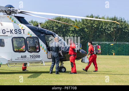 Paramedics and doctor of Kent, Surrey, Sussex Helimed air ambulance helicopter attending incident in England, UK. Aircraft is AgustaWestland AW169. - Stock Photo
