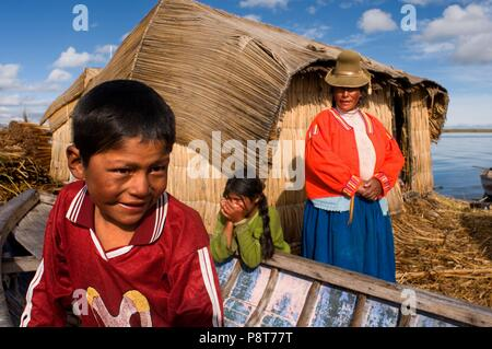 Uros Island, Lake Titicaca, peru, South America. A family around his house, made of totora, on one of the Uros islands. January 2018   usage worldwide - Stock Photo