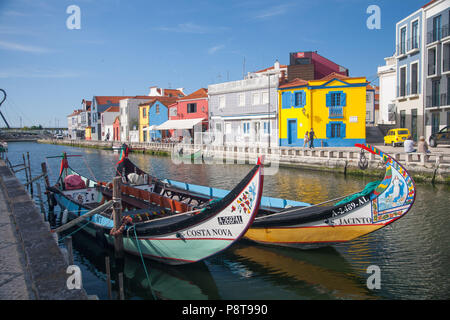 Two colourful Moilceiros (boats originally used for collecting seaweed) moored near traditional fishermen's houses on a canal in Aveiro, Portugal - Stock Photo