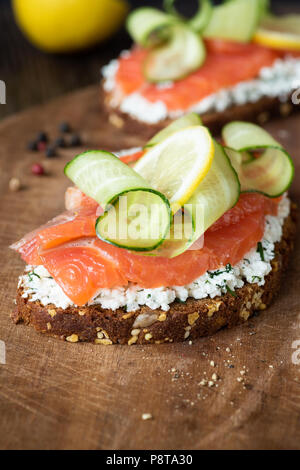 Tasty smoked salmon sandwich with cream cheese, cucumber and slice of lemon on wooden board, closeup view, selective focus - Stock Photo