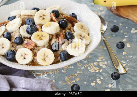 Hot breakfast of healthy oatmeal with pecans, bananas, blueberries and honey over a rustic background. Image shot from overhead. - Stock Photo