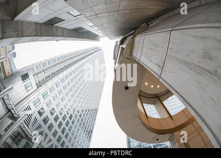 Wide angle perspective looking up at buildings on Canada Square, Canary Wharf, London - Stock Photo