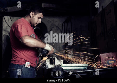 Turkish worker using an angle grinder on metal in an indoor workplace. - Stock Photo