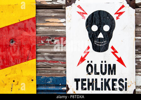 White metal danger of death warning sign in Turkish with a skull and lightning on wooden background. - Stock Photo
