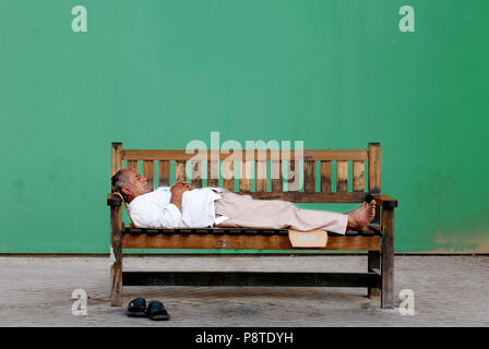 Poor old homeless Indian man sleeping on a wooden bench in front of a green wall. - Stock Photo