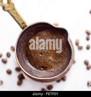 Turkish coffee in a traditional hand-made jezve - Stock Photo