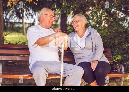 Smiling senior couple sitting together on a park bench - Stock Photo