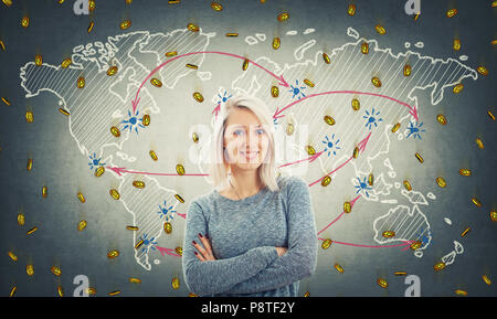 Cheerful blonde with blue eyes and crossed hands stand over world map background and a lot of golden coins fall down like rain. Global virtual currenc - Stock Photo