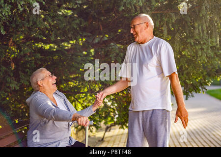 Seniors in park- Smiling old man caring wife in the park - Stock Photo